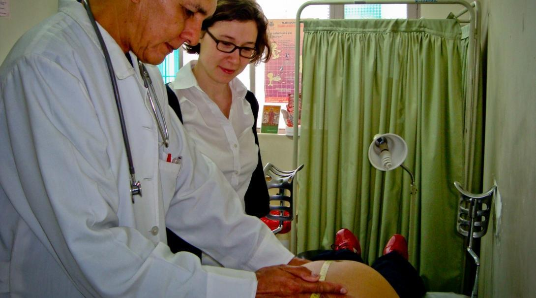A local doctor treats a pregnant woman at a hospital while a student doing her Midwifery internship abroad watches.